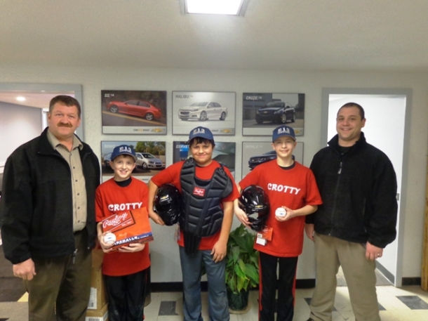 Jon Andrus and Shane Crotty of Crotty Chevrolet present Brandon Arnink, Jeffery Powell and Brendan Zajac, Players in the Corry Little League with new equipment for the upcoming season.